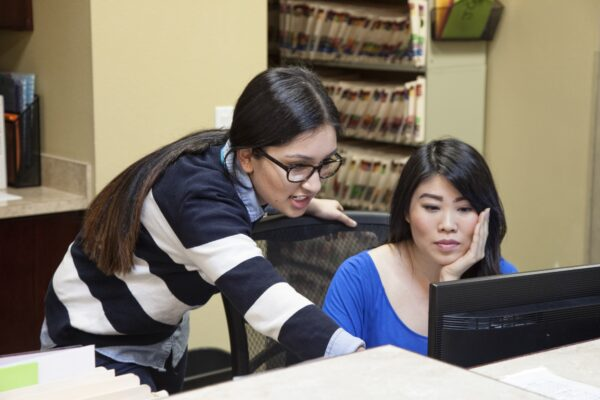 Asian woman and east indian woman working on a computer in a medical office.